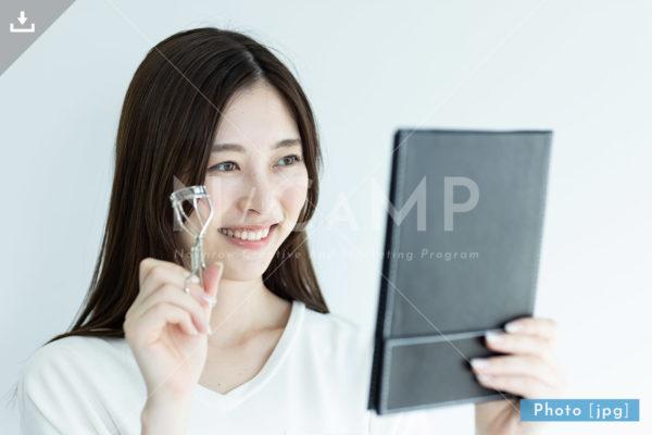 【写真素材】鏡を見てビューラーをする女性